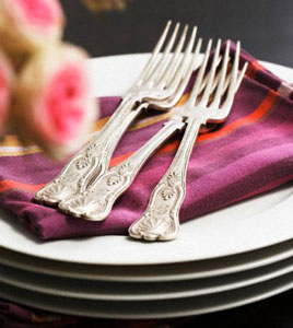 Forks and fabric napkins on pile of plates